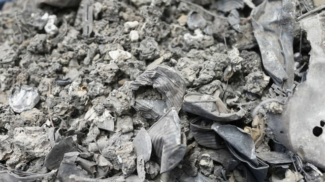Graue trockene Masse mit zahlreichen Metallteilen