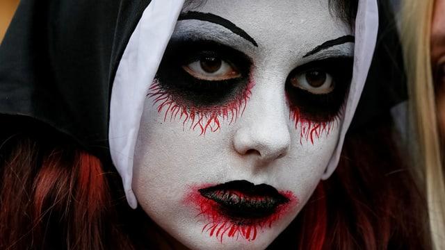 Nahaufnahme einer Person mit weiss geschminktem Gesicht und schwarzen Augen und Mund