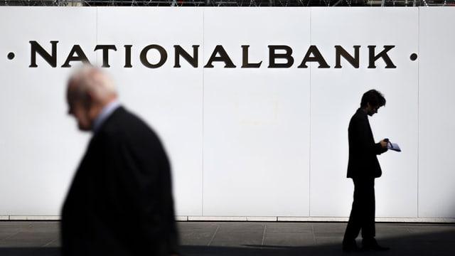Bauschutzwand der Nationalbank am Berner Bundesplatz mit Aufschrift «Nationalbank». Davor stehen Passanten.