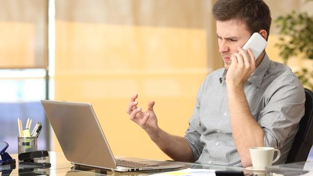 Ein junger Mann mit dem Handy vor seinem Laptop.