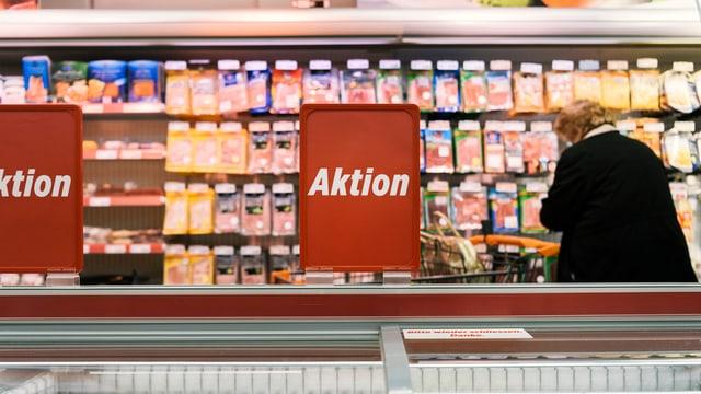 Eine Frau steht vor der Fleischauslage eines Detailhändlers.