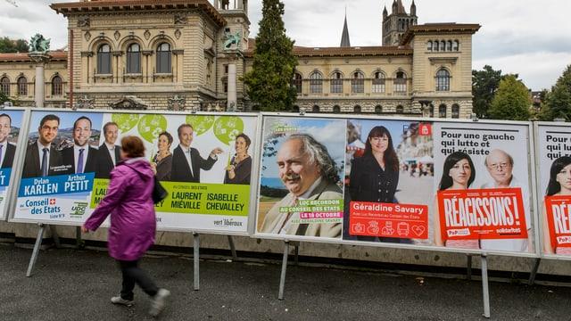 Eine Frau geht vor Wahlplakaten durch.