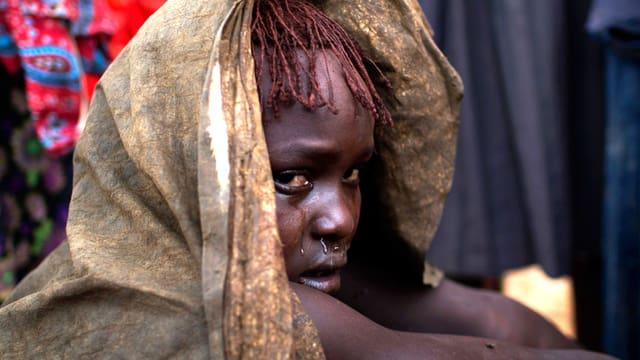 Ein kenianisches Mädchen ist in eine Decke gehüllt und weint.