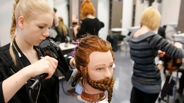 Eine Jugendliche frisiert die Haare eines Puppenkopfes in einem Coiffeur-Salon.