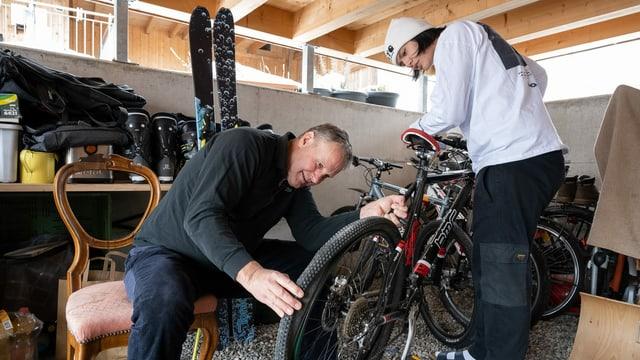 Ein Mann repariert mit einem Jugendlichen in der Garage ein Fahrrad.