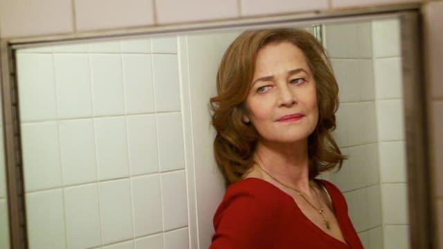 Eine Frau betrachtet sich im Spiegel.