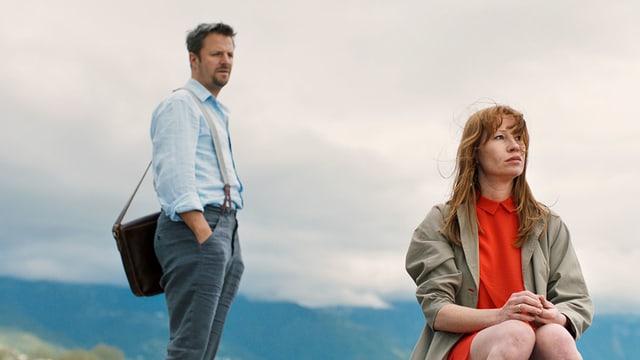 Ein junges Paar in den Bergen: Sie sitzt im Vordergrund, er steht ein paar Schritte hinter ihr.