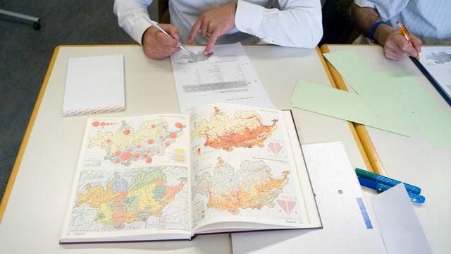 Männer füllen ein Formular aus, davor Schweizer Karten.