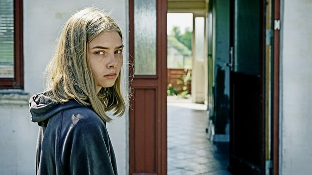 ein Mädchen mit blonden Haaren schaut skeptisch in die Kamera