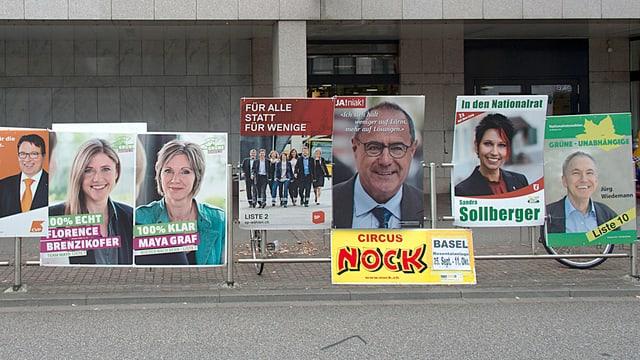 Sieben Wahlplakate und ein gelbes Zirkusplakat an einem Geländer montiert.