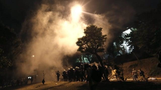 Demonstranten und Polizisten in einem Park in Istanbul bei Nacht in einer Tränengaswolke.