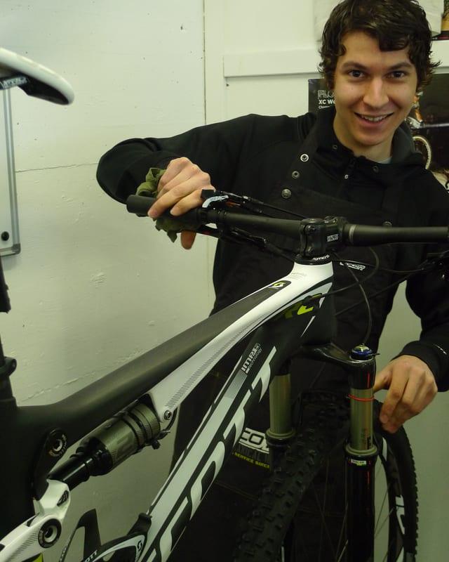 Zu sehen ist ein junger Man in einem schwarzen Pullover, der an einem aufgebockten Mountain-Bike herumhantiert.