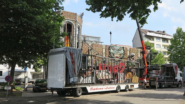 Lastwagen-Anhänger vor dem Rohbau eines dreistöckigen Geisterhauses