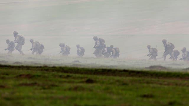Nato-Manöver in Rumänien: Vollbepackte und bewaffnete Soldaten rennen über ein Feld, fotografiert aus grosser Entfernung.