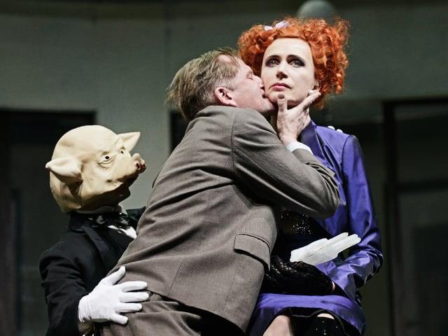 Ein Mann küsst eine Frau mit roter Perücke auf die Wange.