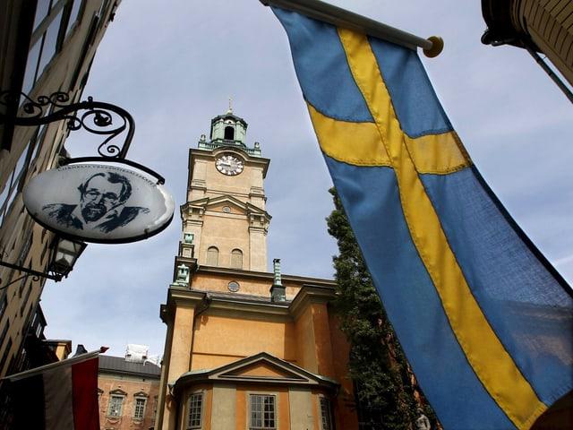 Blick auf eine Kirche mit einer Schweden-Flagge im Vordergrund.