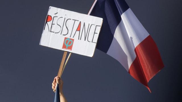 Eine Tricolore und ein Plakat mit der Aufschrift Resistance (Widerstand).