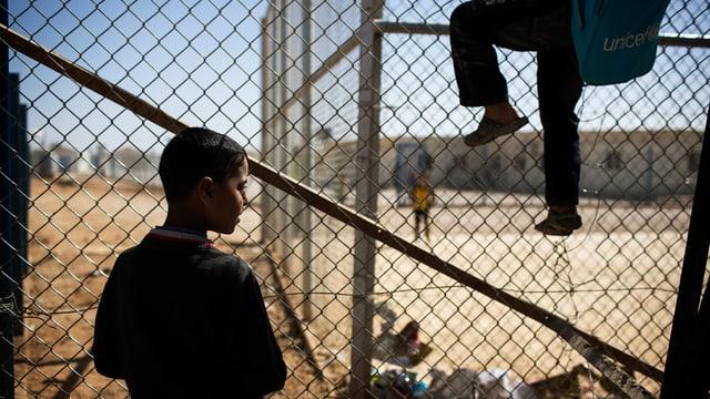 Zwei Kinder in einem Flüchtlingslager klettern über einen Zaun.