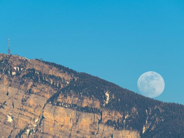 Aufgehender Mond über einem Bergkamm, es ist noch hell, die Mondscheibe ist weisslich verfärb.t