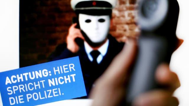 Ein Telefonhörer, dahinter ein Plakat mit der Aufschrift: Hier spricht nicht die Polizei.