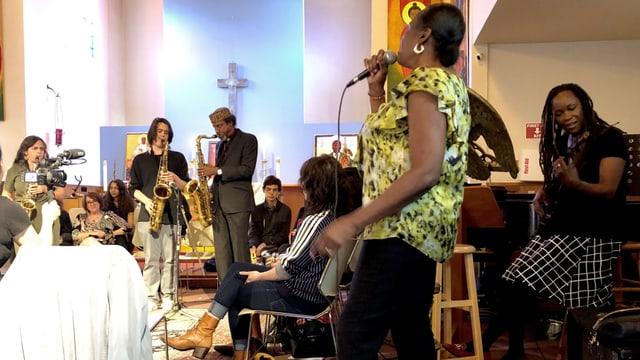 Frauen und Männer musizieren in einer Kirche.