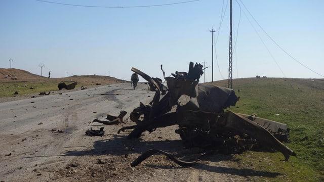 Überreste eines Autos nach einem Bombenanschlag auf einer Strasse von Mossul.
