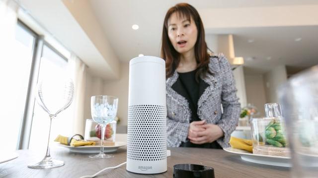 Symbolbild: Eine Frau spricht zum Amazon-Alexa-Lautsprecher/Mikrofon.