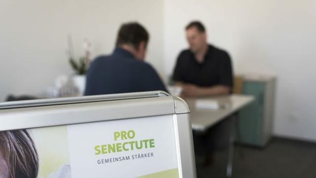 Zwei Personen in einem Gespräch. Im Vordergrund eine Tafel mit dem Logo von Pro Senectute.