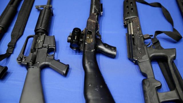 Drei Gewehre sind auf einem Tisch aufgelegt.
