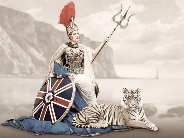 Eine Frau mit einem Schild mit der Grossbritannien-Flagge draus. Neben ihr ein Tiger.
