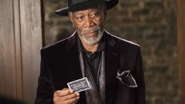 Morgan Freeman als Thaddeus Bradley hält eine Spielkarte in der Hand.