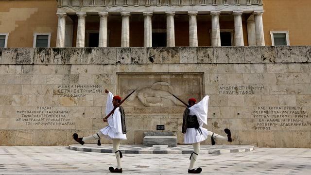 Zwei Wachmänner gehen vor dem Parlamentsgebäude in Athen im Stechschritt auf und ab.
