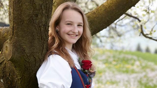 Arlette lehnt sich an Baumstamm. Sie trägt eine Tracht. Im Hintergrund eine Blumenwiese.