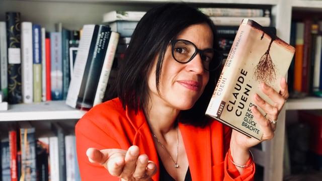 Annette hält das Buch  «Der Mann, der das Glück bringt» von Claude Cueni in den Händen und schaut fragend drein.