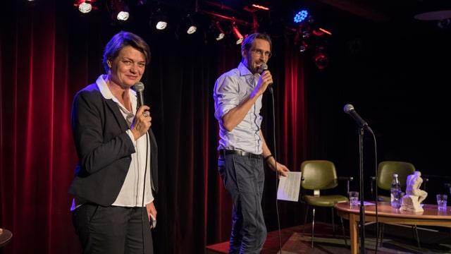 Anne Baecher und Yves Bossart je mit einem Mikro in der Hand auf der Bühne.