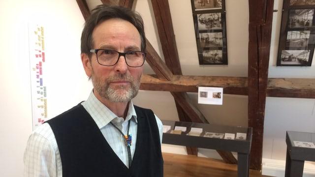 Mann mit Bart und Brille. Im Hintergrund Fotos an den Wänden.
