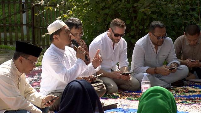 Männer sitzen auf Teppichen rund um einen Imam, der in ein Mikrofon spricht