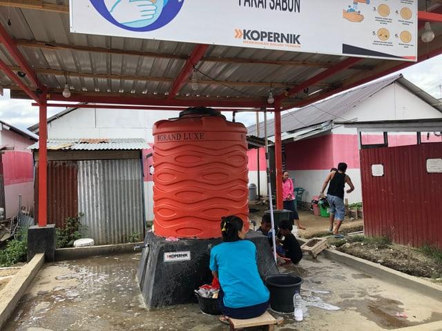 Frau wäscht in Zeltlager ausserhalb von Palu ihre Wäsche am Boden.