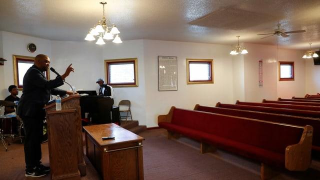 Schwarzer Prediger spricht von einem Pult. Er steht vor leeren Kirchenbänken.