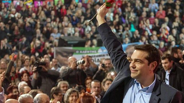 Alexis Tsipras von Syriza vor einer Menschenmenge. Er hält mit der rechten Hand eine Rose in die Höhe.