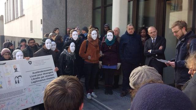 Eine Gruppe von Menschen, darunter einige Maskierte, haben einen übergrossen Ausländerausweis. Baschi Dürr steht dabei und hört sich die Rede eines Aktivisten an.