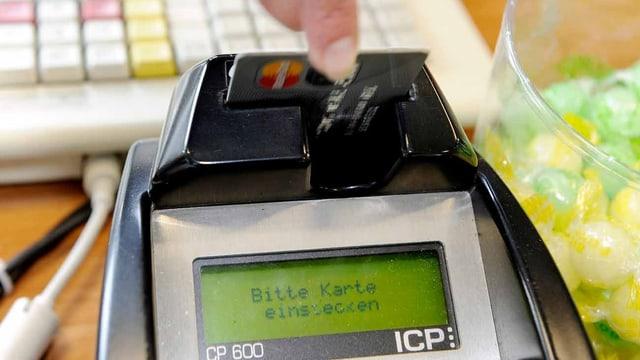 Ein Frau schiebt eine Karte in den Bezahlterminal.