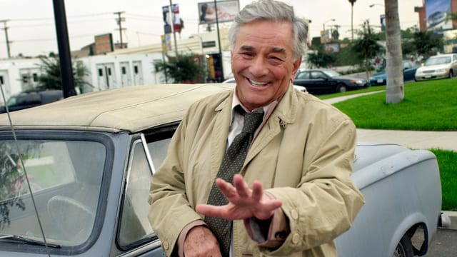 Inspektor Columbo in seinem Trenchcoat vor seinem Peugeot