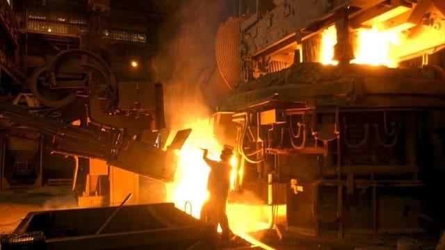 Stahlproduktion mit gelbleuchtenden Öfen.