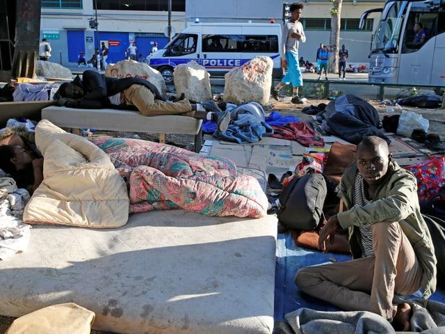 Menschen auf alten Matrazen auf der Strasse.