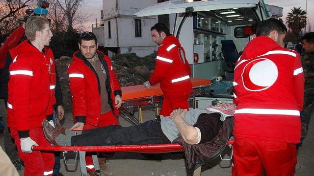Mann auf Bahre liegend, Mitarbeiter des Roten Halbmonds