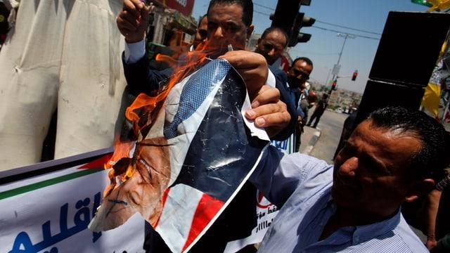 Männer verbrennen ein Poster von Trump.