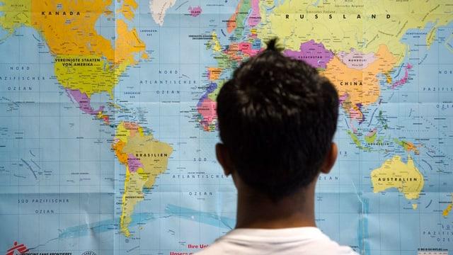 Ein Asylbewerber studiert eine Weltkarte.