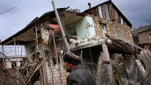Mann vor zerstörtem Haus.
