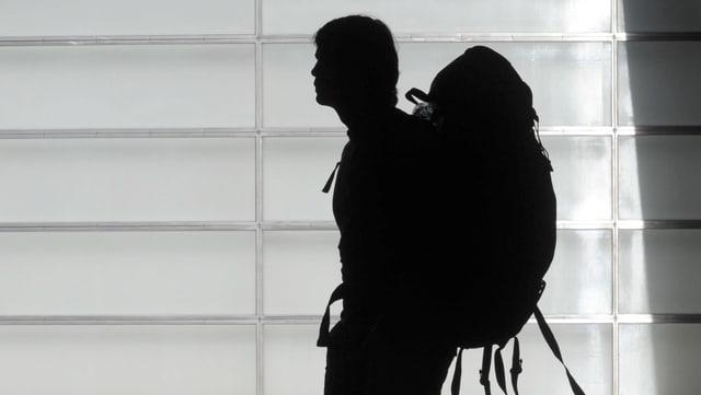 Ein Mann mit grossen Rucksack im Gegenlicht.